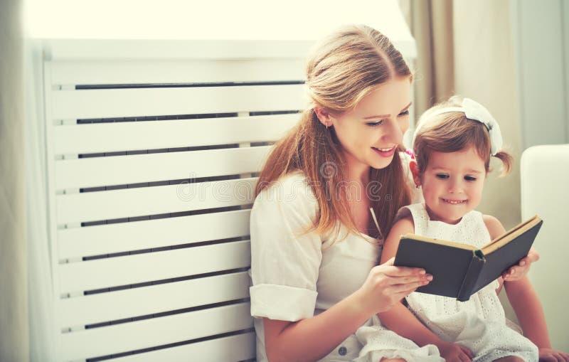 Livro de leitura feliz da menina da criança da mãe da família imagens de stock