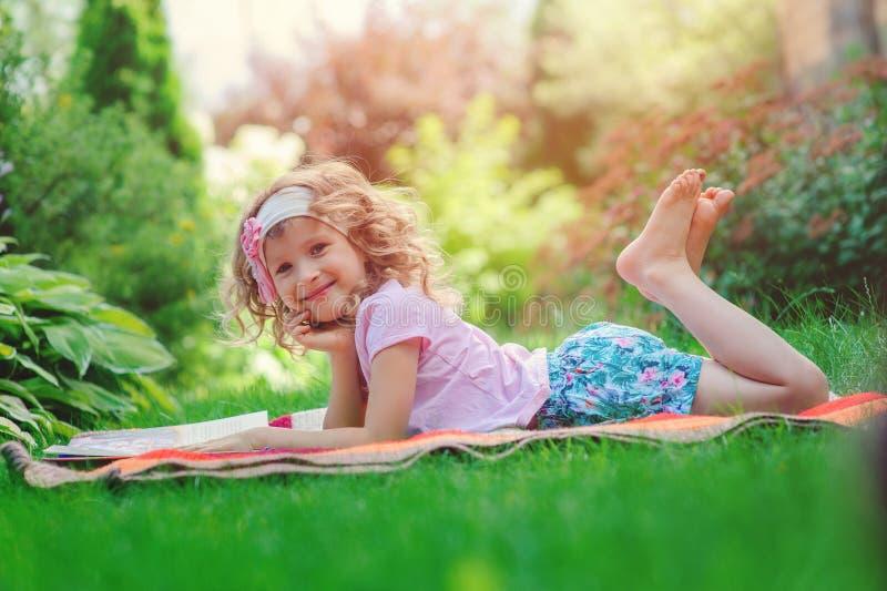 Livro de leitura feliz da menina da criança em férias de verão no jardim foto de stock royalty free