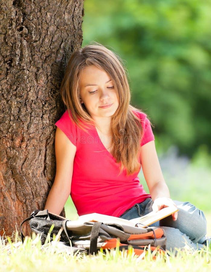 Livro de leitura feliz da menina do estudante imagens de stock