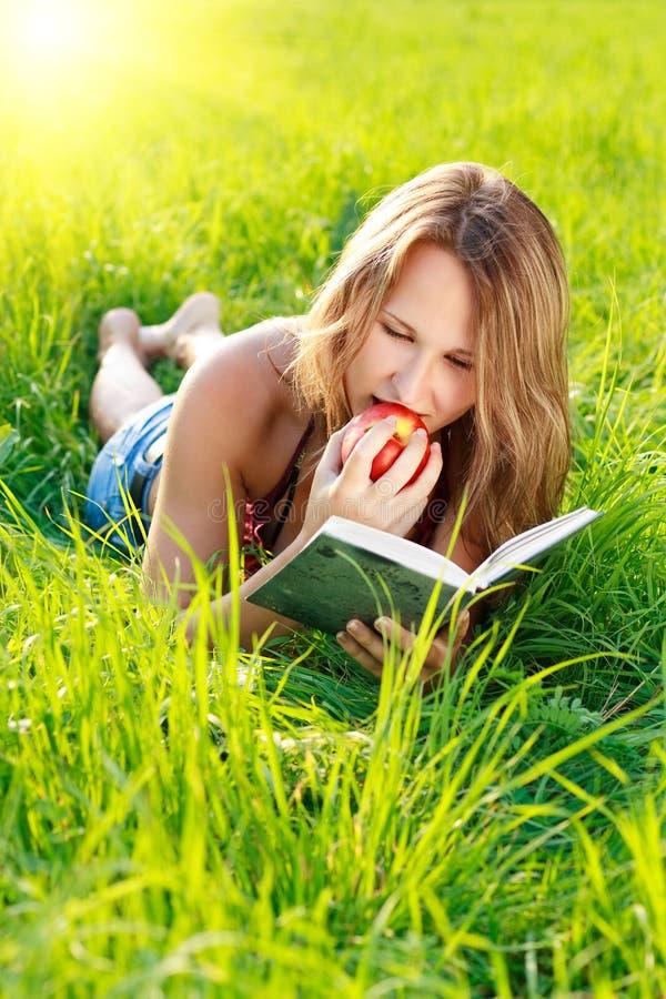 Livro de leitura feliz da mulher com Apple à disposicão foto de stock