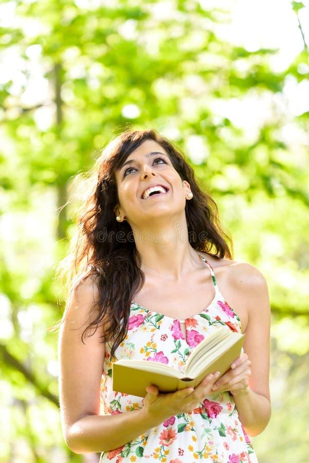 Livro de leitura feliz da mulher na mola fotografia de stock royalty free
