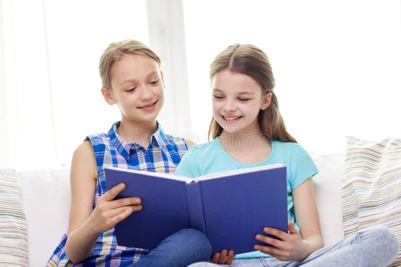 Livro de leitura feliz de duas meninas em casa foto de stock royalty free