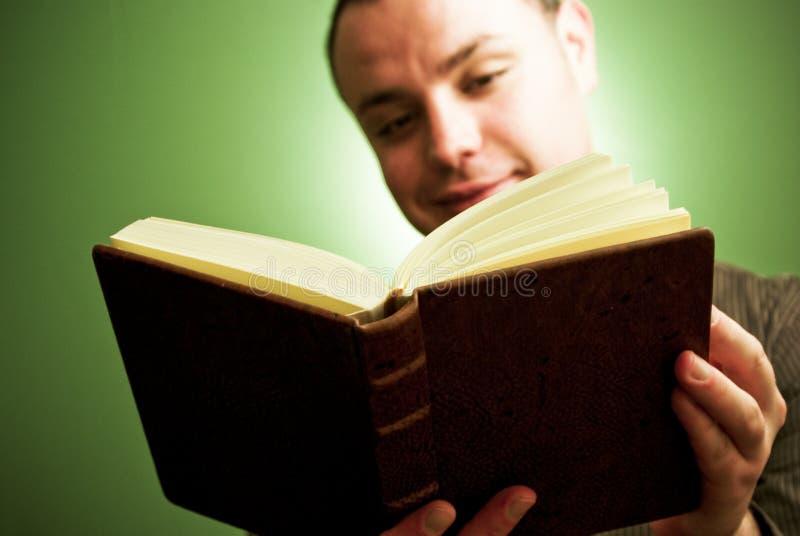 Livro de leitura feliz do homem novo imagem de stock royalty free
