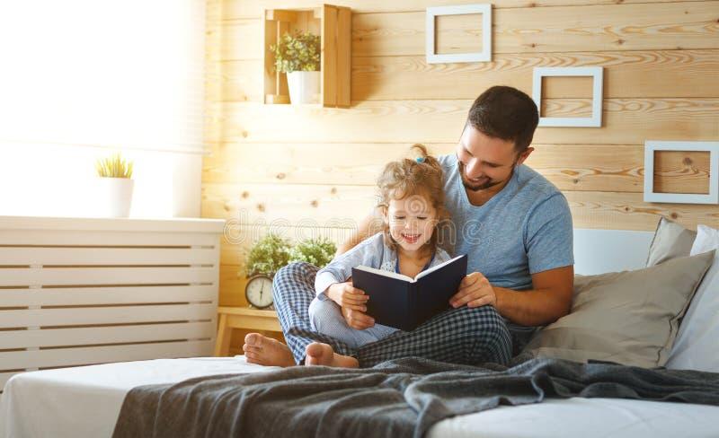 Livro de leitura feliz do pai e da filha da família na cama imagens de stock royalty free