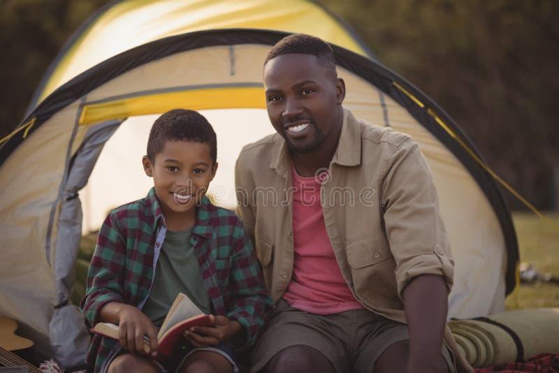 Livro de leitura feliz do pai e do filho no parque imagens de stock