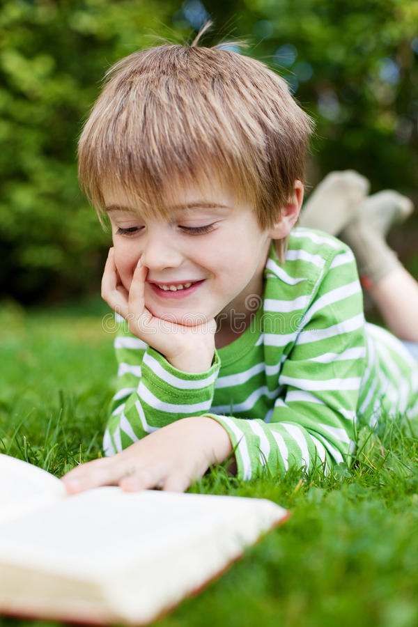 Livro de leitura feliz do rapaz pequeno no jardim foto de stock royalty free