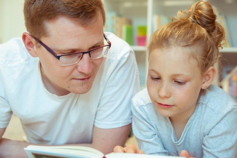 Livro de leitura feliz novo do pai com filha bonito em casa foto de stock