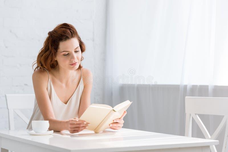 livro de leitura focalizado da jovem mulher com o copo de café na tabela imagem de stock royalty free