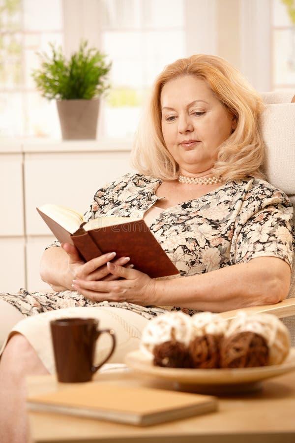 Livro de leitura idoso da mulher foto de stock royalty free