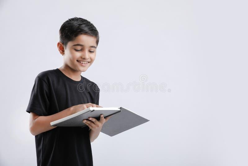 Livro de leitura indiano/asiático pequeno bonito do menino isolado sobre o fundo branco fotografia de stock