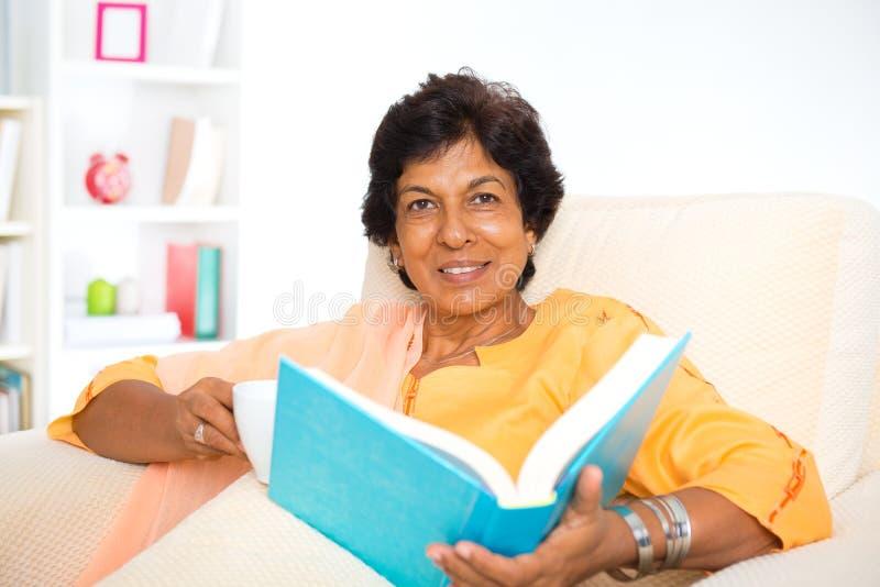 Livro de leitura indiano maduro da mulher imagem de stock