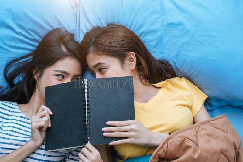 Livro de leitura lésbica asiático bonito dos pares junto e encontrando-se na cama Conceito dos estilos de vida e dos amantes Vida foto de stock