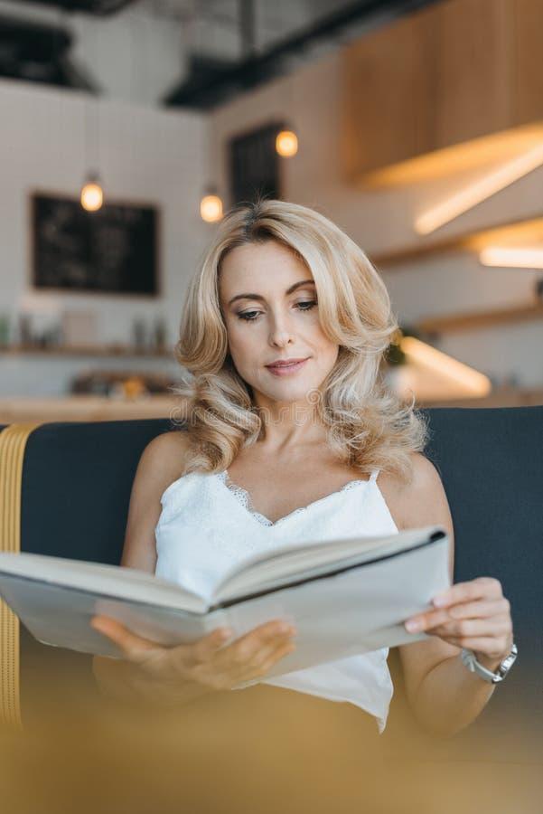 livro de leitura louro concentrado bonito da mulher ao sentar-se fotografia de stock royalty free