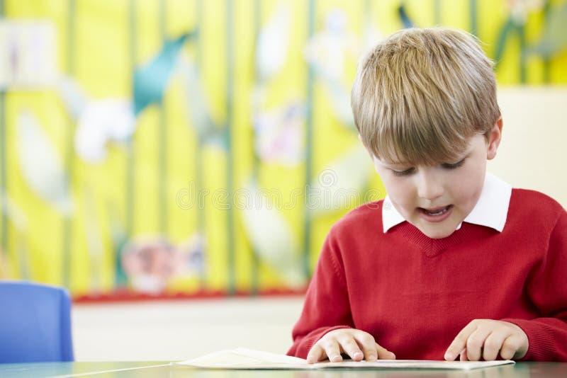 Livro de leitura masculino do aluno na tabela imagens de stock royalty free