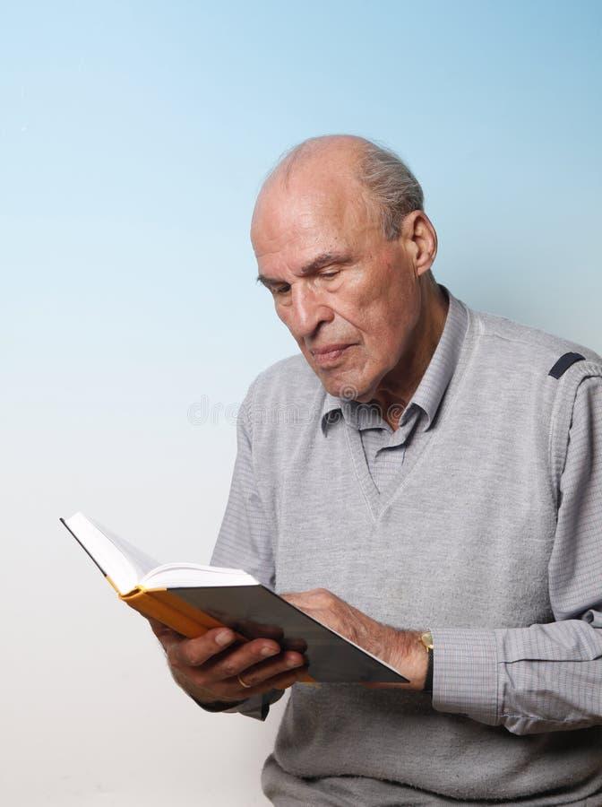 Livro de leitura masculino sênior fotografia de stock royalty free