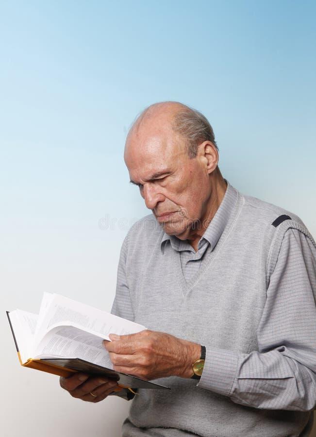 Livro de leitura masculino sênior imagem de stock royalty free