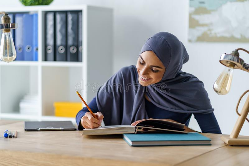 Livro de leitura muçulmano fêmea do estudante fotografia de stock royalty free