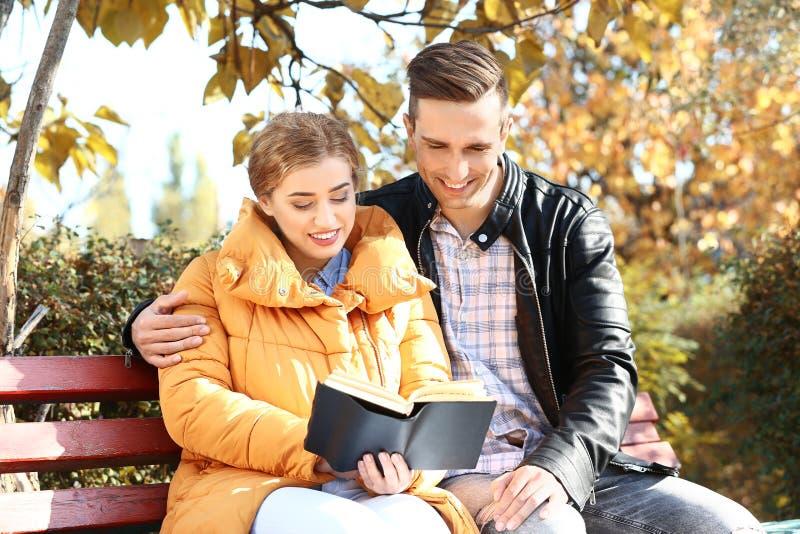 Livro de leitura novo de amor dos pares no parque do outono foto de stock