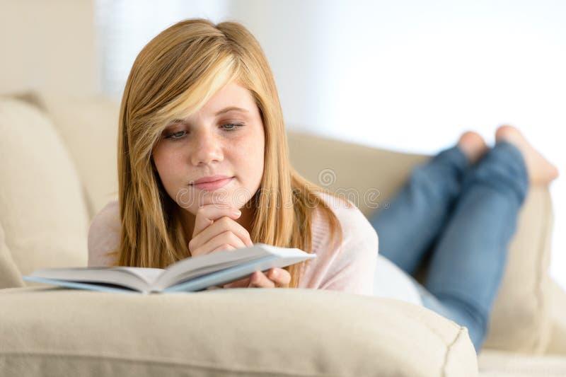 Livro de leitura novo da menina do estudante no sofá foto de stock royalty free