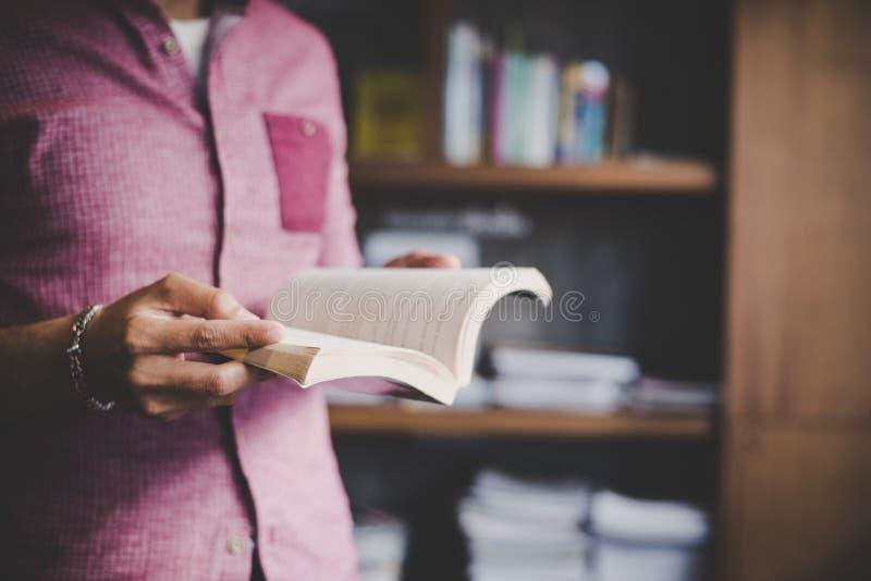 Livro de leitura novo do homem do moderno na biblioteca fotografia de stock