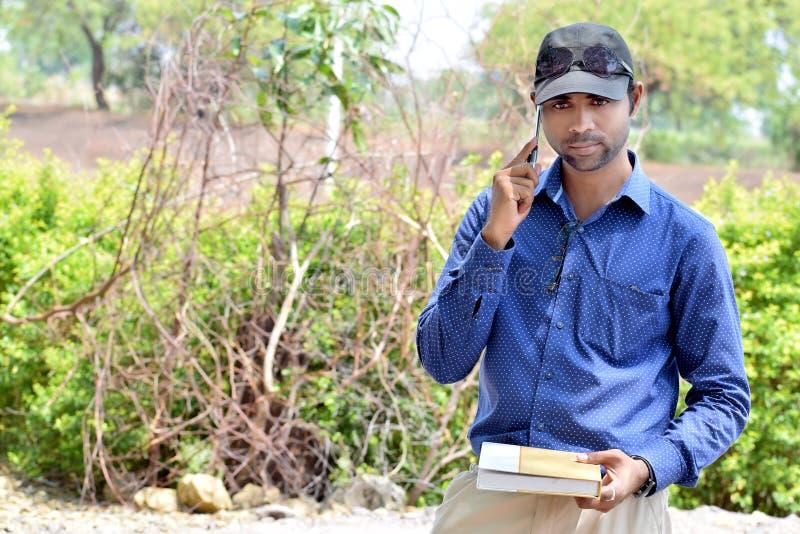 Livro de leitura novo indiano à moda feliz do homem de negócios exterior foto de stock