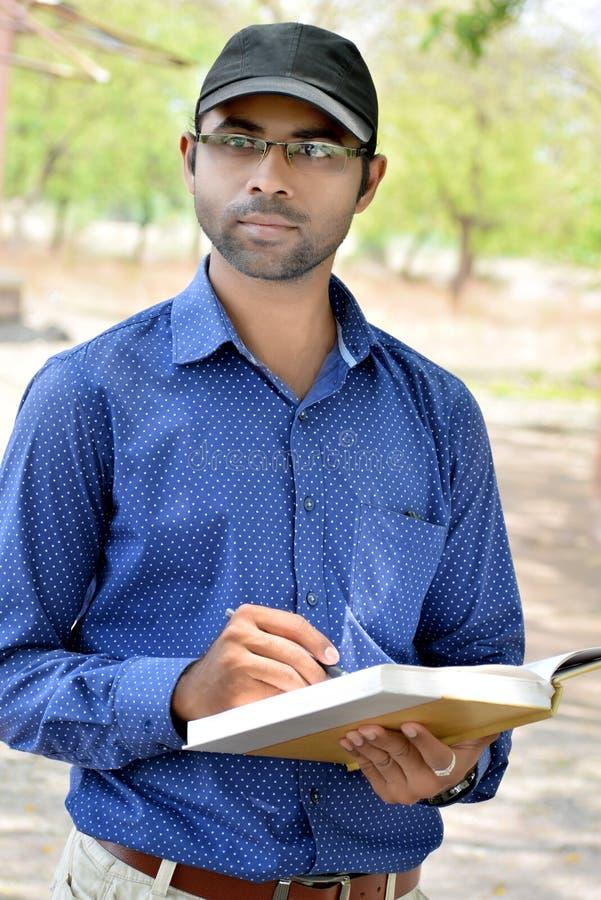 Livro de leitura novo indiano à moda feliz do homem de negócios exterior imagem de stock
