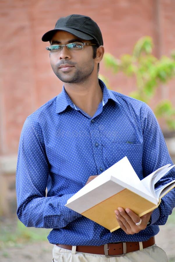 Livro de leitura novo indiano à moda feliz do homem de negócios exterior imagens de stock