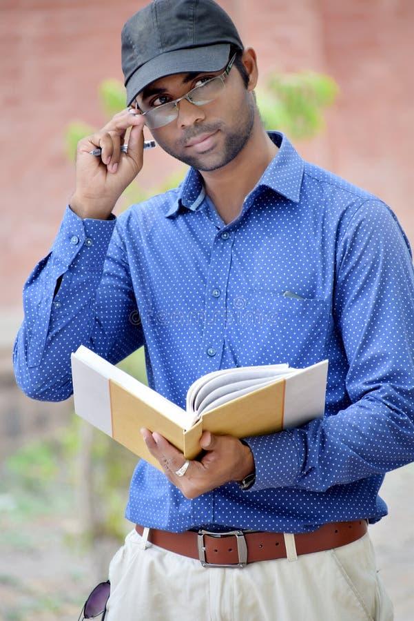 Livro de leitura novo indiano à moda feliz do homem de negócios exterior fotos de stock royalty free