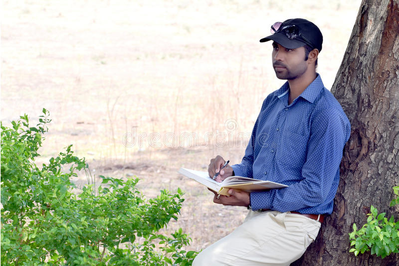 Livro de leitura novo indiano à moda feliz do homem de negócios exterior imagens de stock royalty free