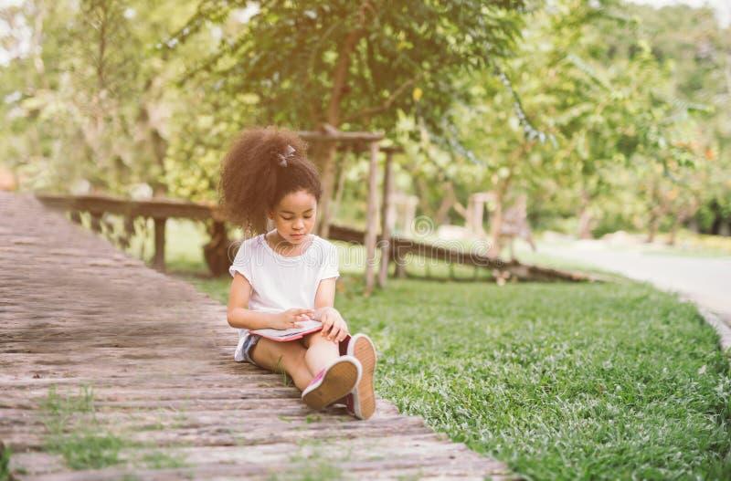 Livro de leitura pequeno da menina da criança do Afro entre o jardim verde do prado dos pontos foto de stock royalty free