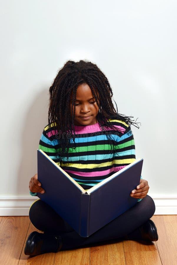 Livro de leitura preto pequeno da menina foto de stock