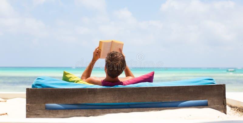 Livro de leitura relaxado do homem no vadio luxuoso que aprecia férias de verão na praia bonita fotos de stock