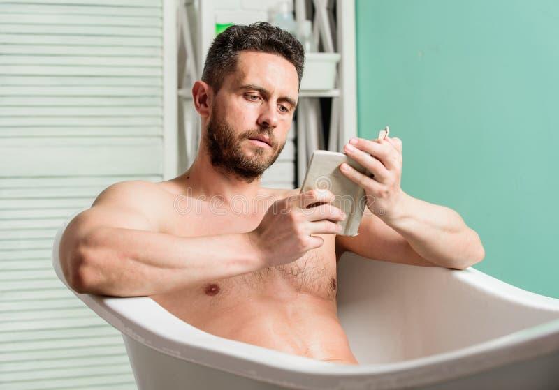 Livro de leitura relaxado do indiv?duo ao relaxar no banho quente Relaxe em casa Abrandamento total Higiene pessoal Sistema nervo fotos de stock royalty free