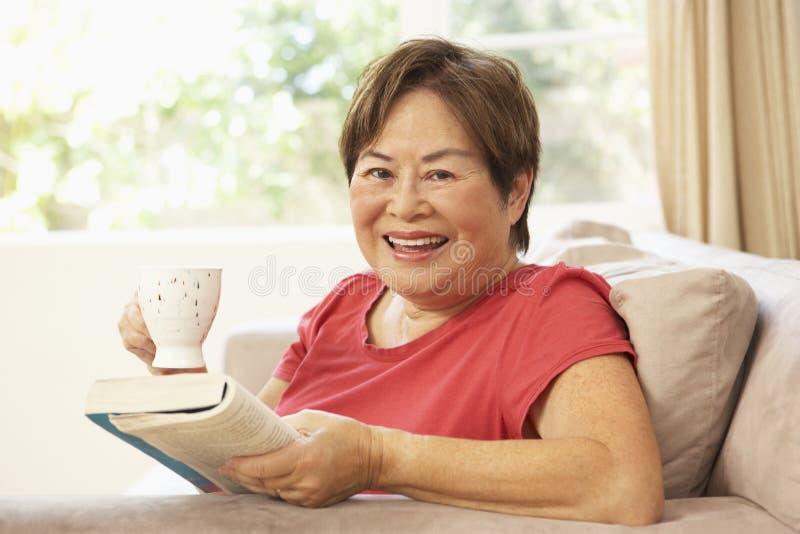 Livro de leitura sênior da mulher com bebida em casa fotografia de stock royalty free