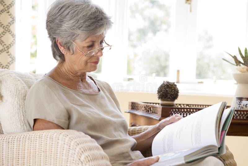 Livro de leitura sênior da mulher em casa imagens de stock