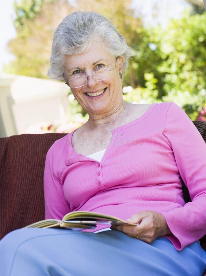 Livro de leitura sênior da mulher fora fotografia de stock royalty free