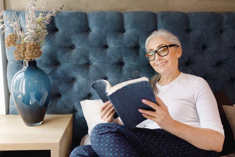 Livro de leitura s?nior da mulher fotos de stock royalty free