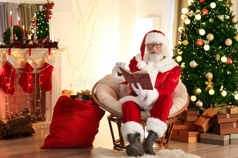 Livro de leitura de Santa Claus na sala decorada para o Natal fotos de stock royalty free