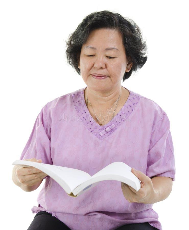 Livro de leitura superior da mulher adulta imagem de stock