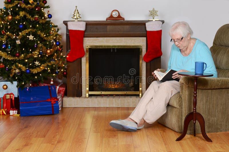 Livro de leitura superior da mulher na sala de visitas do Natal imagem de stock