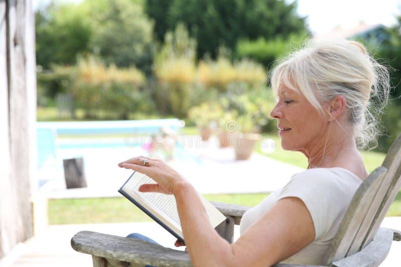Livro de leitura superior da mulher pela piscina imagem de stock