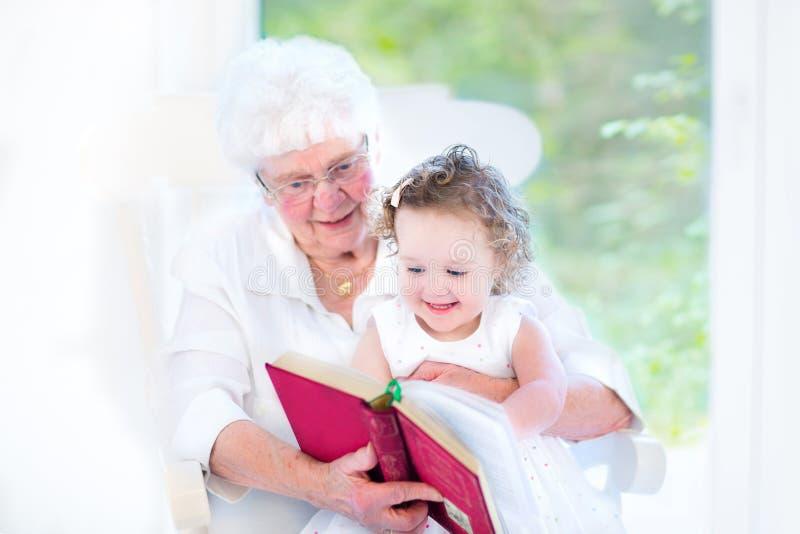 Livro de leitura superior da senhora a sua neta imagens de stock royalty free