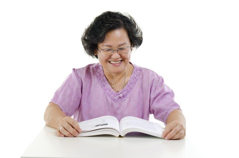 Livro de leitura superior feliz da mulher adulta foto de stock