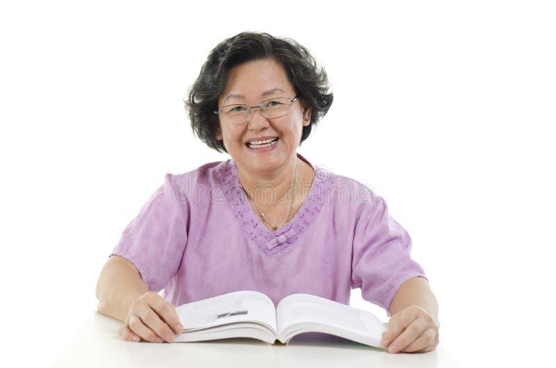 Livro de leitura superior sábio da mulher adulta foto de stock