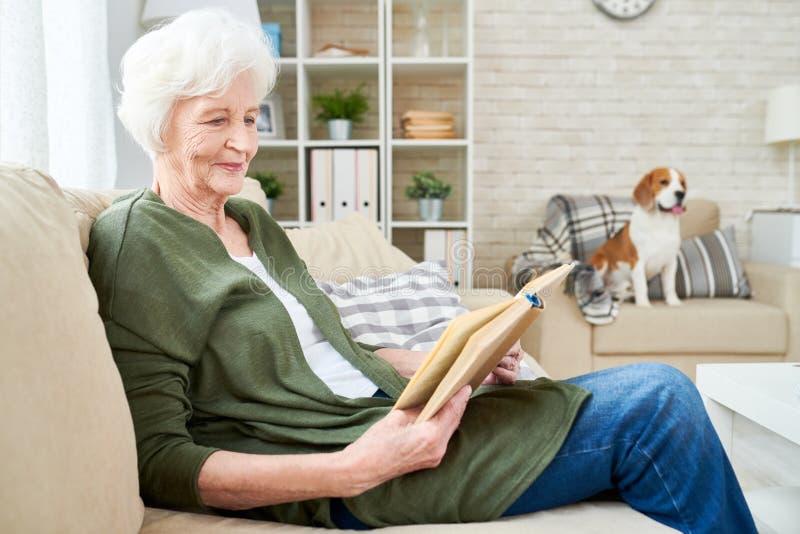 Livro de leitura superior de sorriso da mulher em casa fotografia de stock royalty free