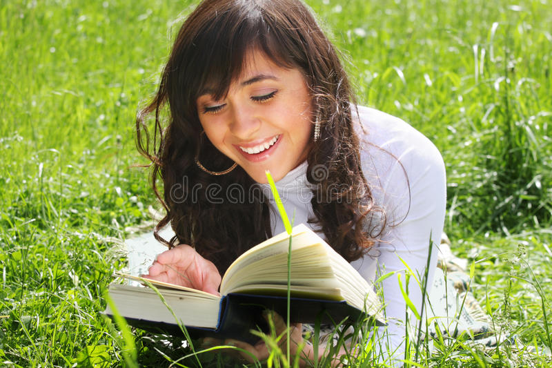 Livro de leitura triguenho de sorriso na grama imagens de stock royalty free