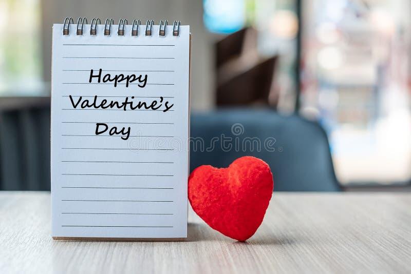 Livro de nota com a decoração vermelha da forma do coração no fundo de madeira da tabela saúde Insursnce, amor, casamento, românt fotografia de stock royalty free