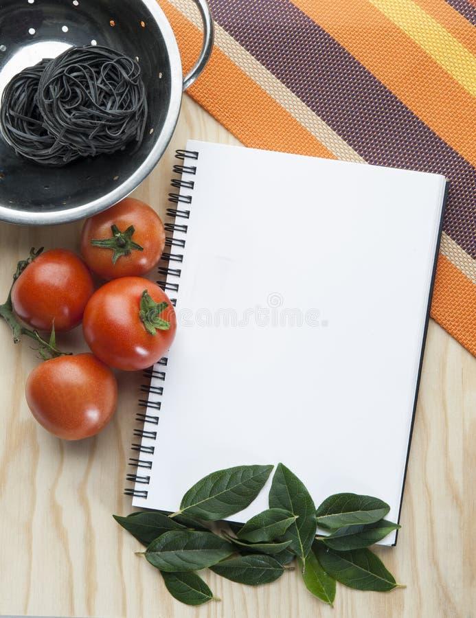 Livro de nota da cozinha em uma toalha de mesa com tomates uma bacia foto de stock