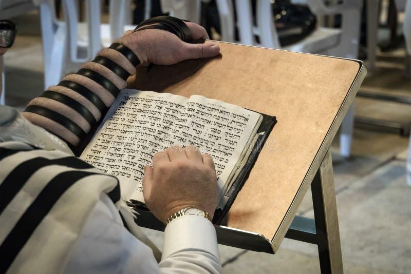 Livro de oração da leitura do judeu da religião Torah na tabela na frente da parede lamentando na cidade velha do Jerusalém Israe imagem de stock royalty free