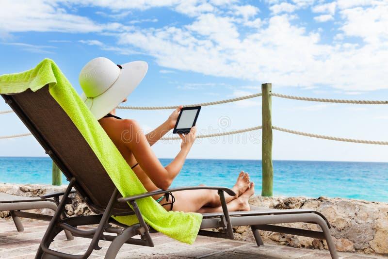 Livro de papel eletrônico para a cadeira do sol foto de stock royalty free